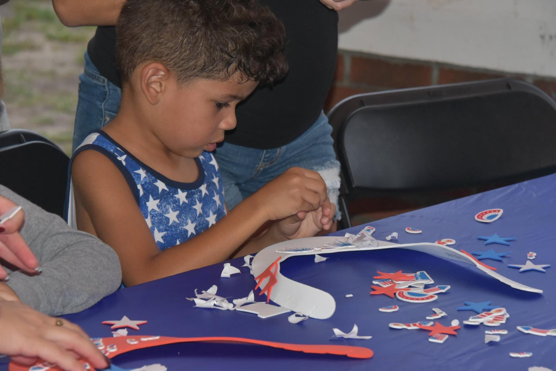 This is a photo of a child creating a patriotic craft at the 2019 Monumental 4th of July.