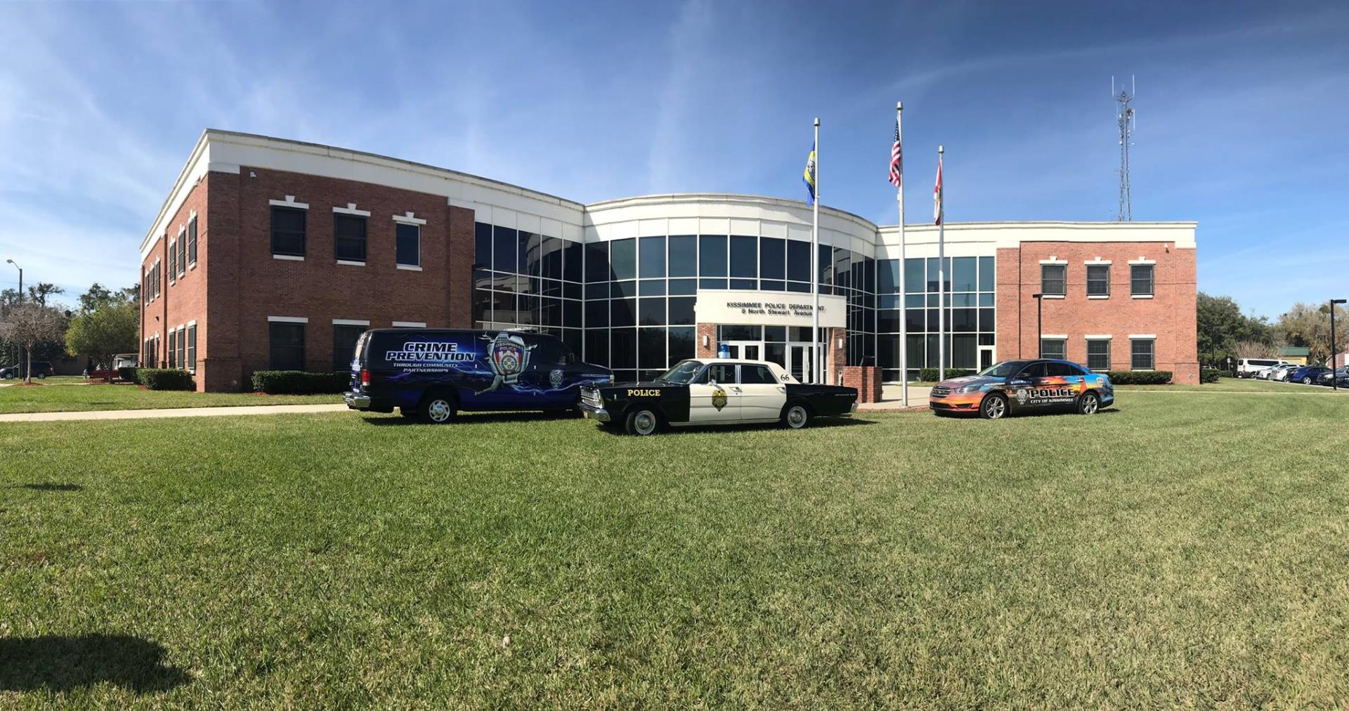 This is a photo of Kissimmee Police Department with different police vehicles parked in front of the main entrance.