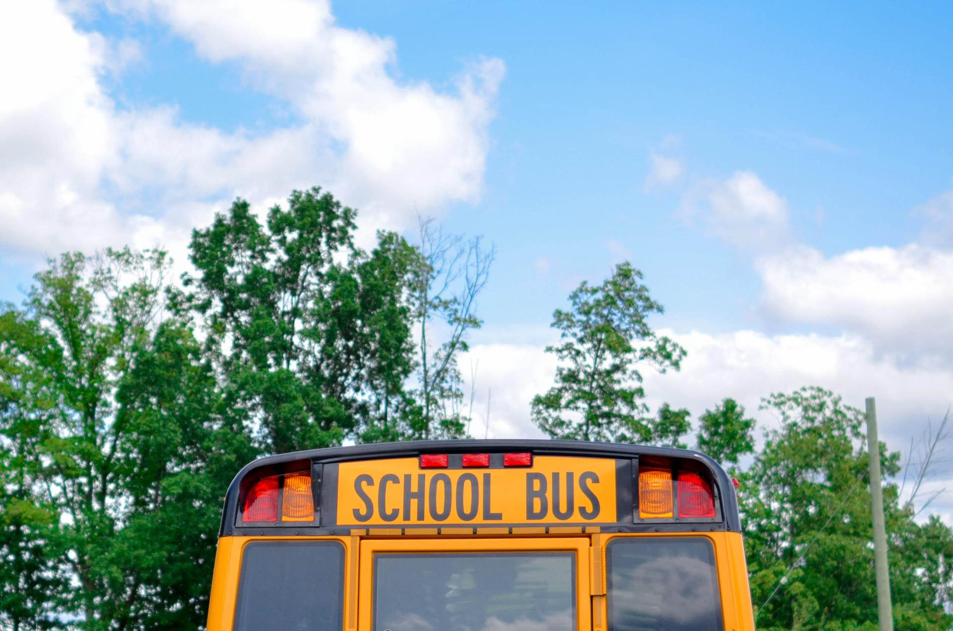 This is a photo of a school bus with trees and blue skies in the background. City of Kissimmee back to school.