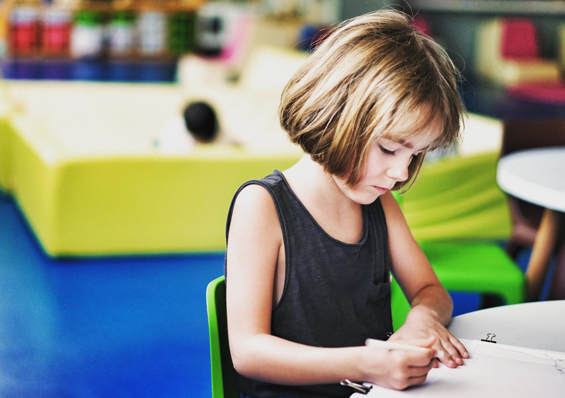 This is a photo of a girl sitting at a table writing.