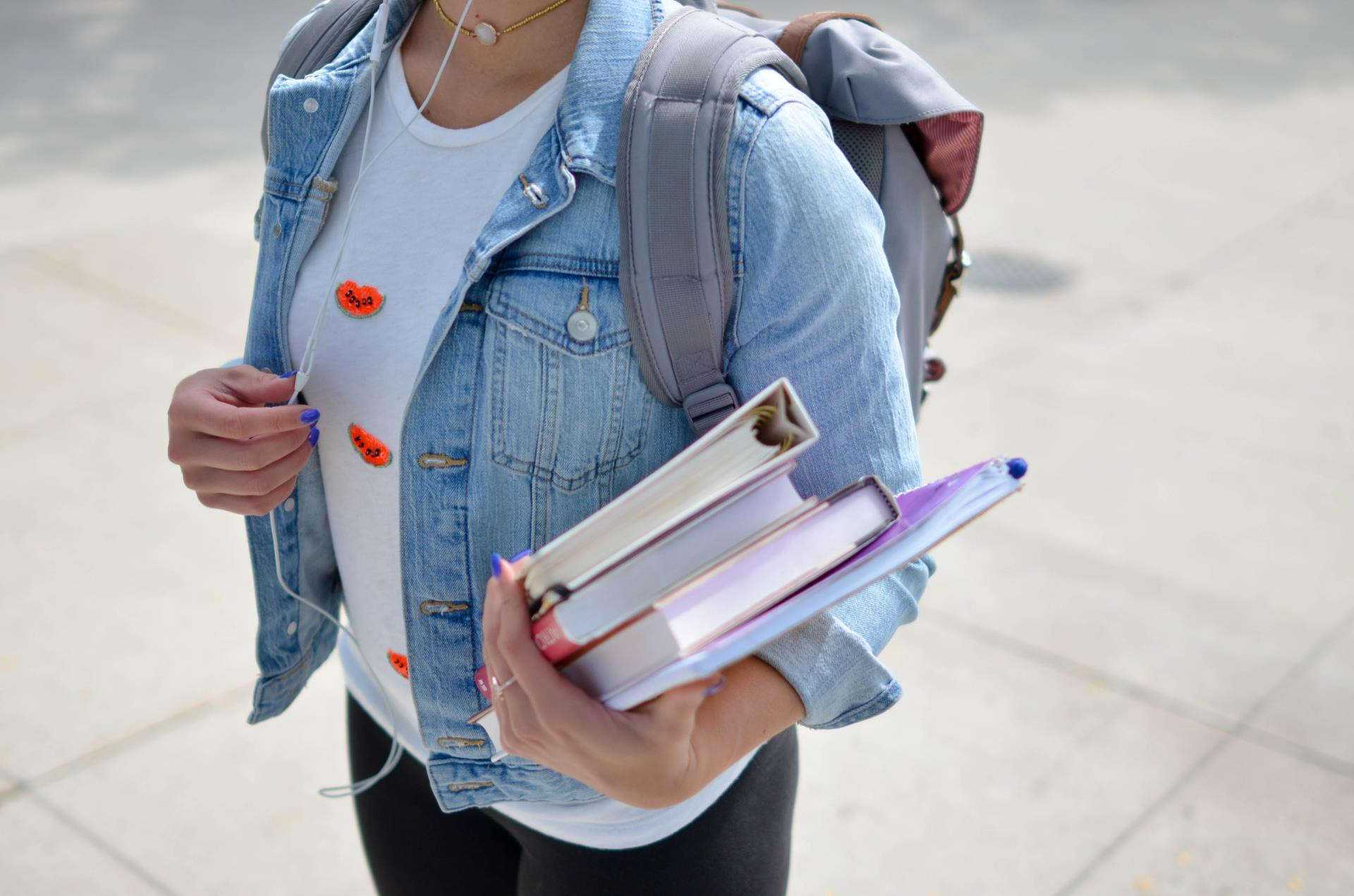 This is a photo of a girl carrying notebooks and wearing a backpack.