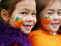 This is a photo of two girls with pumpkin face paint on.