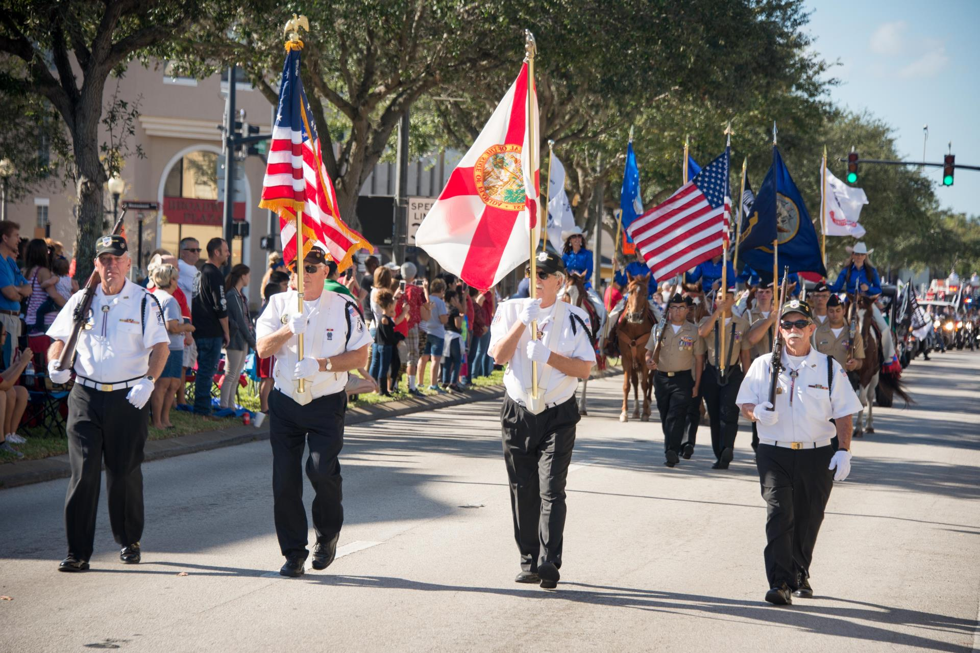 This is a photo of people marching in downtown Kissimmee for the Veterans Day Parade.